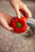 Woman washing a red pepper