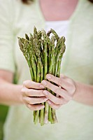 Woman holding bunch of fresh asparagus