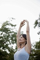 Woman doing yoga outdoors (thumbnail)