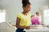 Girl putting money into piggy bank (thumbnail)