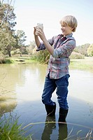 Boy collecting specimens from pond