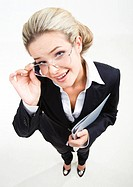 Above view of modern business woman wearing black suit and glasses and staring at camera with positive expression