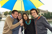 Four young people standing under an umbrella, Paris, France