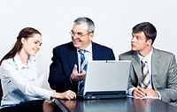 Communication of elderly boss with his managers in front of laptop at business meeting