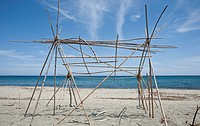 Frame of beach hut on sand, Prunete, Corsica