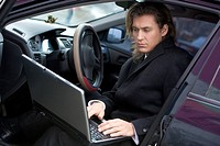Portrait of handsome man typing on laptop while sitting in car