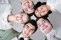 Below view of five friends looking at camera with their heads next to each other