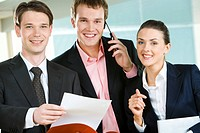 Portrait of happy business group looking at camera with smiles with businessman speaking on the phone in the middle