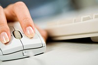 Close_up of female hand on white mouse during computer work