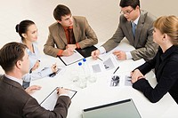 Group of five businesspeople discussing different questions gathered together around the table