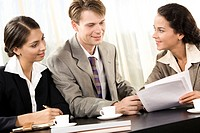 Photo of friendly man and woman sitting in office and discussing business plan with their colleague near by