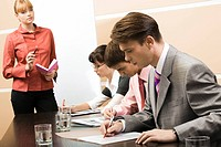 Image of executive managers learning documents with business leader standing near by
