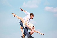 Image of passionate couple dancing over blue sky background