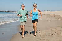 Senior couple jogging on beach