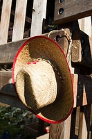 Cowboy hat hanging on wooden fence
