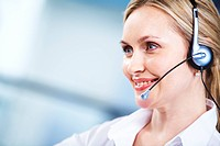 Portrait of executive female in headset smiling during communication