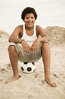 Portrait of boy sitting on top of football