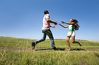 Photo of young man and woman running to each other outdoors
