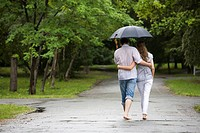 View of couple a back under umbrella walking down the park in autumn