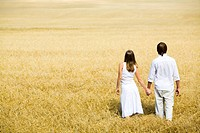 Image of couple holding by hands and walking along the field