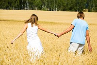 Rear view of couple holding by hands