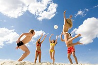 Photo of five friends playing with ball on sand