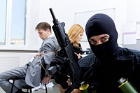 Photo of terrorist in balaclava holding gun on background of bound office workers