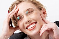 Image of happy woman in eyeglasses touching her face and laughing