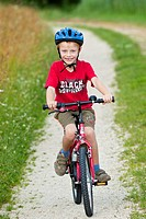 A boy, 7 years, riding a bicycle on a dirt road
