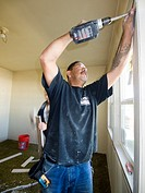 Construction workers repair a foreclosed home that was vandalized in Los Angeles, California, United States  Black Shirt: Marco Moreno / White Pants: ...