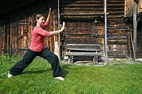 Woman, early 40s, doing Tai Chi in front of a wooden hut in the Swiss Alps, Switzerland, Europe
