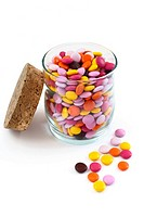 Colorful candy coated chocolate in a glass jar with a cork lid on a white background. No sharpening