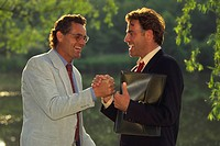 2 glad business people shaking hands