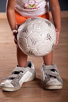 Three years old little girl playing with a soccer ball with man's sneakers