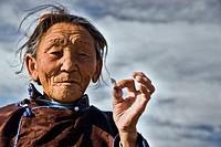 Old Mongolian woman smoking a cigarette, Mongolian steppe