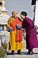 Woman talking to a Buddhist monk at the Gandantegchinlen Khiid monastery, Ulaan Bataar, Mongolia