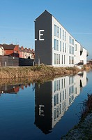 Modern apartments on the Coventry Canal contrasting with old traditional terraced housing to the rear, West Midlands, UK