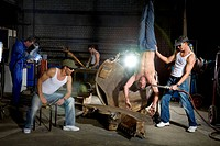 Men in Workshop torturing other Man