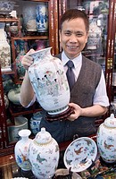 Shop owner showing his antique porcelains, Hong Kong, China