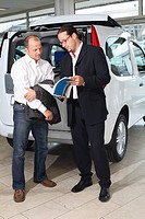 Man and Salesman in Car Showroom