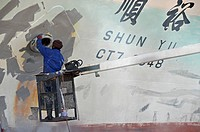 Varnisher applying anti_rust paint, renovation works on a drydock, Cape Town, South Africa