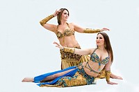 Two beautiful belly dancers dressed in gold and blue, isolated