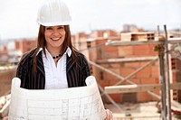 Elegant engineer holding a model in a construction