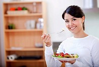 Healthy eating woman with fruit salad smiling .