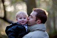 Portrait of a father holding his son in the park, smiling