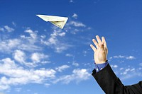 A businessman trying to fly a paper airplane made out of dollar bill, can be used for money concept