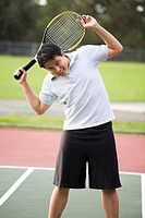 A young asian male stretching before playing tennis