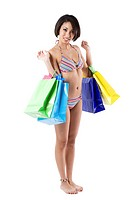 An isolated shot of a beautiful black woman carrying shopping bags