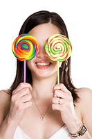 An isolated shot of a beautiful asian woman holding two lollipops covering her eyes