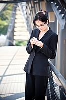 A portrait of a hispanic businesswoman texting outdoor